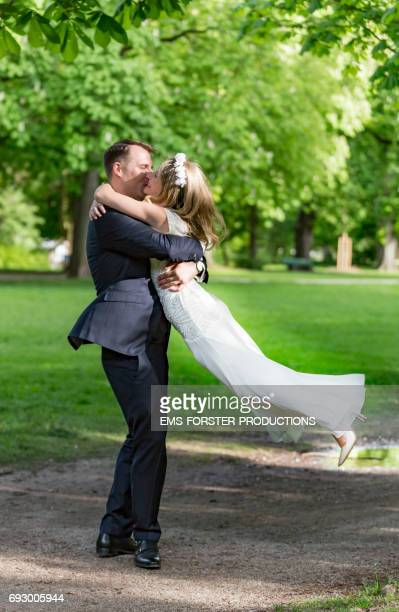 long blonde haired bride wearing floral headband and her white wedding dress gets swung around by her tall brown haired groom in his wedding suit outside in a green park on a sunny day