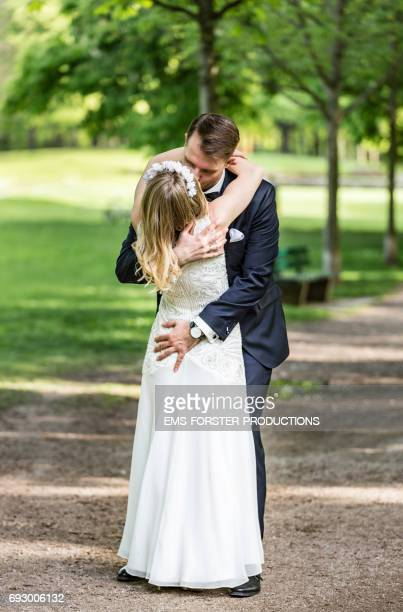 long blonde haired bride wearing floral headband and her white wedding dress gets hugged and kissed by her tall brown haired groom in his wedding suit outside in a green park on a sunny day right after the wedding ceremony