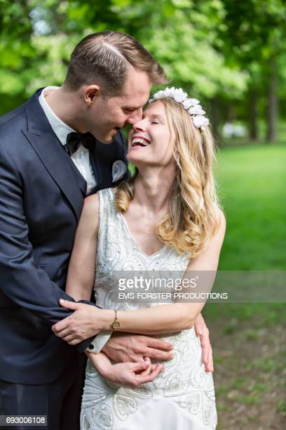 long blonde haired bride wearing floral headband with a bright happy smile wears her white wedding dress together with the happy tall brown haired groom who wears his wedding suit outside in a green park on a sunny day