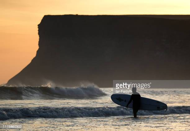 A long boarder heads into the surf as the sun rises over the beach on September 20 2019 in Saltburn By The Sea England Much of the country will be...