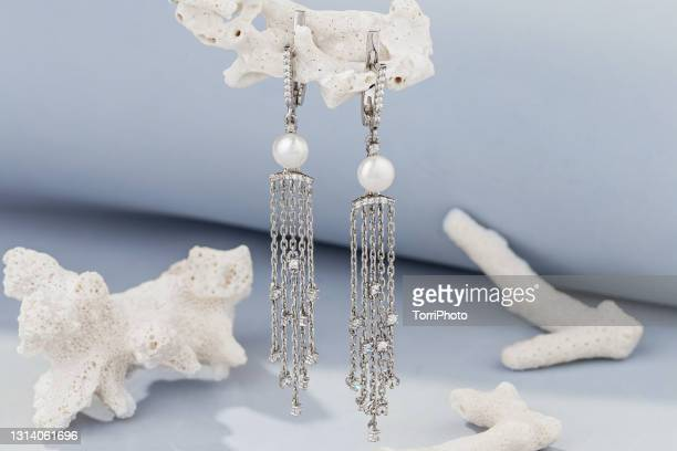 long chains silver earrings decorated with pearls on blue background with white corals - white gold stock pictures, royalty-free photos & images