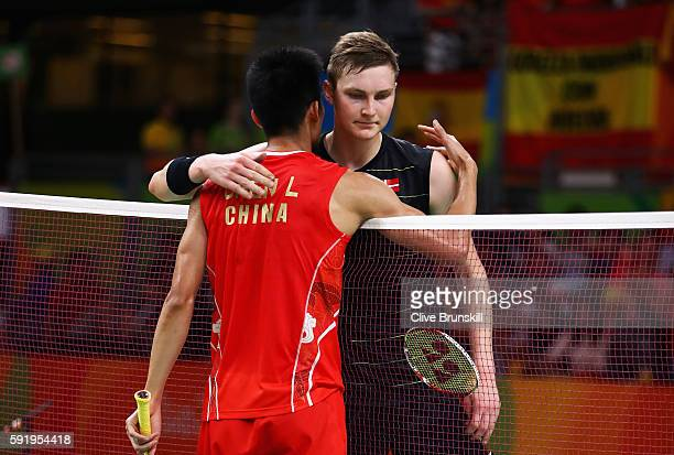 Long Chen of China meets Viktor Axelsen of Denmark at the net after winning the Men's Singles Badminton Semifinal on Day 14 of the Rio 2016 Olympic...