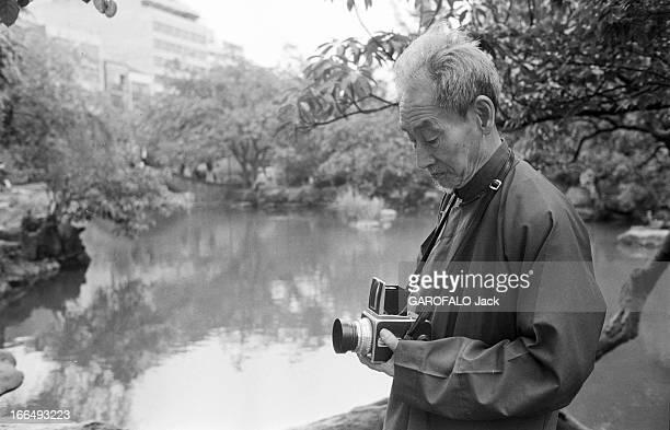 Long ChinSan Shanghai 15 mai 1978 LONGCHINSAN photographe spécialiste des paysages et des photos compositions réglant son appareilo photo devant un...
