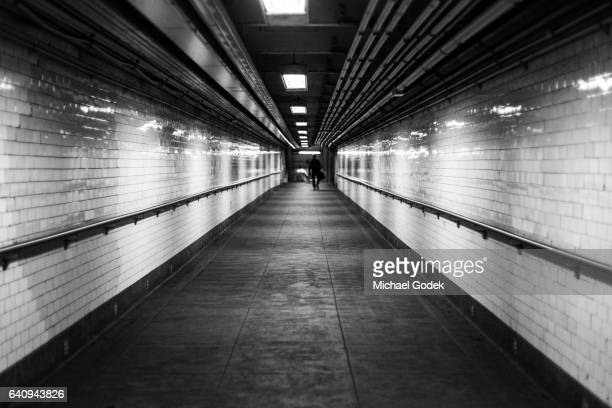 long dark hallway of underground subway entrance with man far off in the distance - horror photos stock photos and pictures