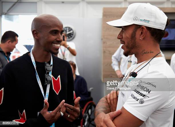 Long distance running legend Sir Mo Farah talks with Lewis Hamilton of Great Britain and Mercedes GP in Mercedes GP hospitality before the Formula...