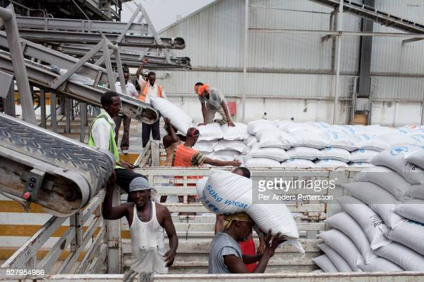 Long distance trucks are loaded with 800 bags of wheat each bound to Ethiopia from WFP World Food Program storage facility in the Djibouti port on...