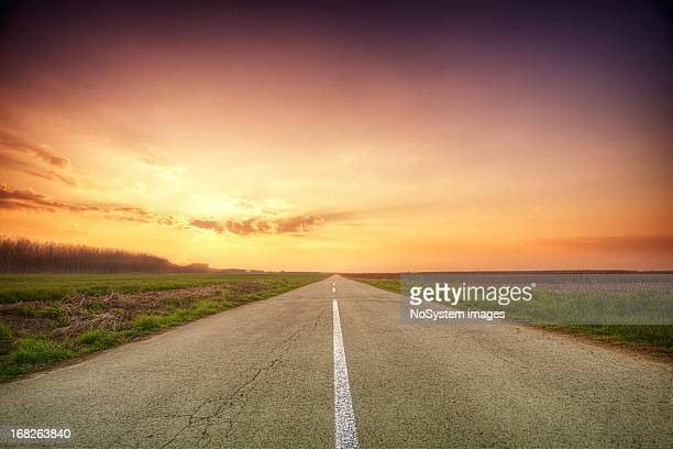 Long empty road between grass patches at sunset