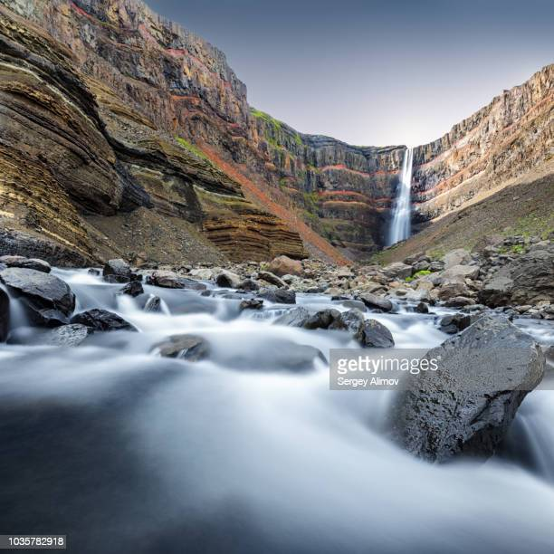 long exposed view of river and hengifoss waterfall in iceland - agua descendente fotografías e imágenes de stock