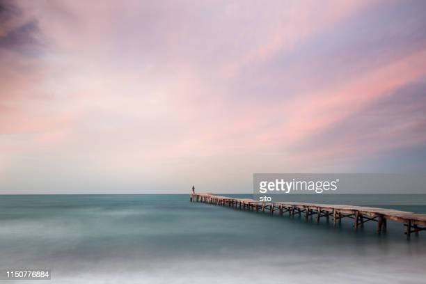 long exposure at playa de muro jetty at sunset, mallorca, spain - muro stock photos and pictures