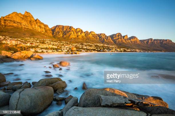 Long exposure at sunset in Camps Bay with Table Mountain and its cable car on the left and the Twelve Apostles to the right, Western Cape, South Africa, Africa