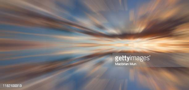 long exposure effect using zoom blur of dramatic sunset sky - zoom background stock pictures, royalty-free photos & images