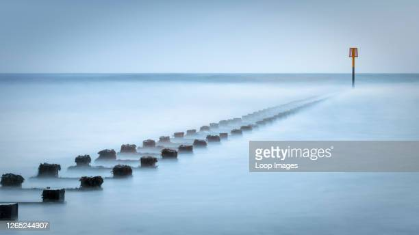 Long exposure image of a breakwater with a warning basket at the end.