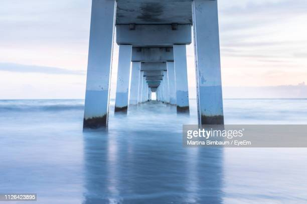 long exposure image of bridge in sea against sky during sunset - fort myers beach stock pictures, royalty-free photos & images