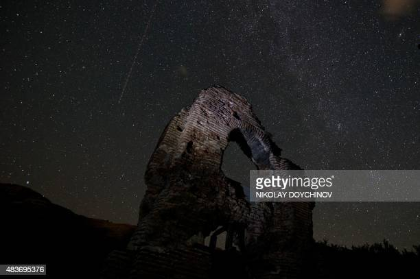 A long exposure image showing an aeroplane passing in the sky during the Perseids meteor shower over the remains of St Ilia Roman early Christian...