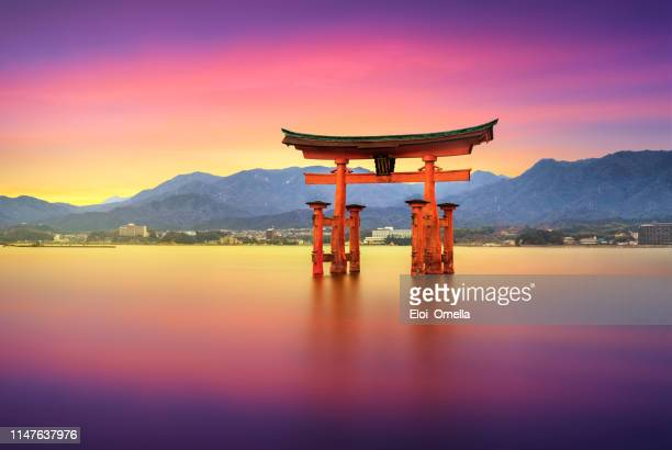 lange blootstelling itsukushima shrine miyajima floating torii gate, hiroshima, japan - japan stockfoto's en -beelden