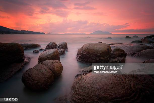 long exposure majestic view of rocky beach during sunset and cloudy day at turtle beach located in singkawang, kalimantan, borneo, indonesia - regency style stock photos and pictures