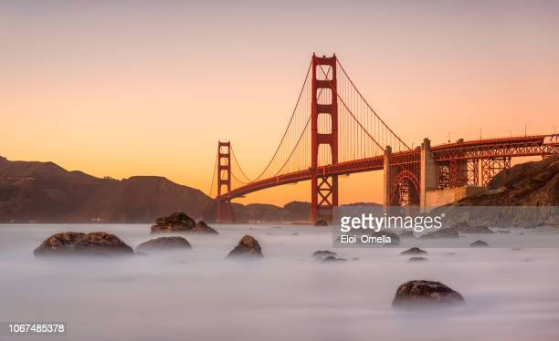 long exposure marshall's beach and golden gate bridge in san francisco california at sunset - san francisco california stock photos and pictures