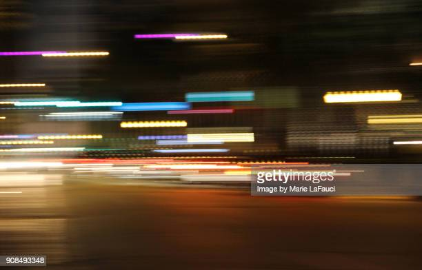 long exposure night time traffic trails with vibrant neon colors - bewegung stock-fotos und bilder