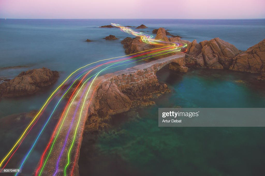 Long exposure of a colorful rainbow of light traces in a beautiful curved path between the rocks over the Mediterranean Sea in the Costa Brava shoreline on sunset. : Stock Photo
