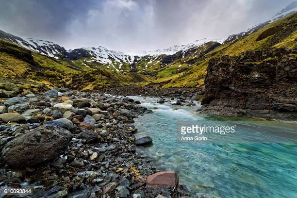 Long exposure of aquamarine stream by Selljavallalaug pool in south central Iceland, spring morning
