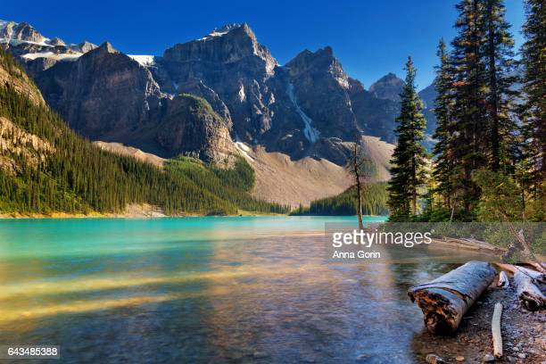 Long exposure of aquamarine waters of Moraine Lake at sunset in summer surrounded by snowcapped peaks, Alberta, Canada