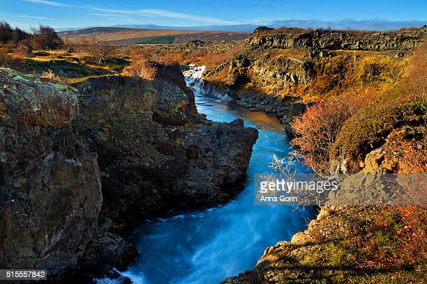 Long exposure of canyon upstream from Hraunfossar waterfalls at sunset in west-central Iceland, autumn