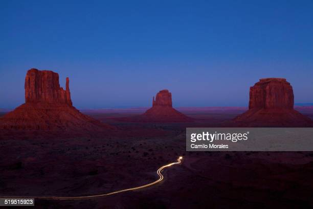 long exposure of car driving past butte rock formations in desert landscape, monument valley tribal park, utah, united states - monument valley tribal park stock photos and pictures