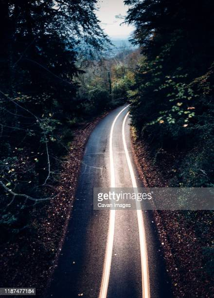 long exposure of car driving with headlights through mountain pass - traffic stock pictures, royalty-free photos & images