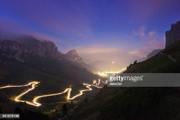 long exposure of car light trails on mountain road leading to passo gardena mountain pass, gardena valley, dolomites, south tyrol, italy - bergpass stockfoto's en -beelden