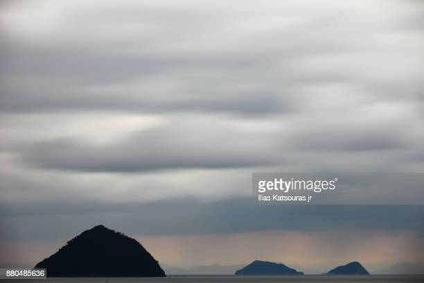 Long exposure of cloudy sky with island of Japanese coast