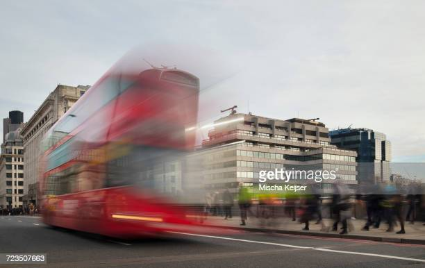 Long exposure of commuters walking on London bridge during rush hour, and double decker bus driving away, London, England