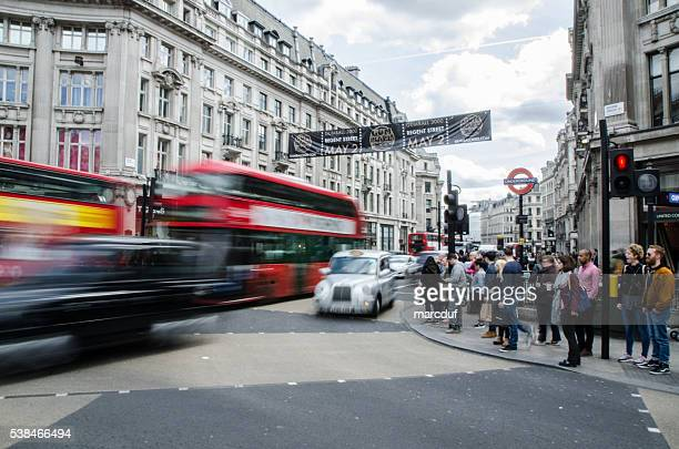 Long exposure of double decker bus and taxi with pedestrians