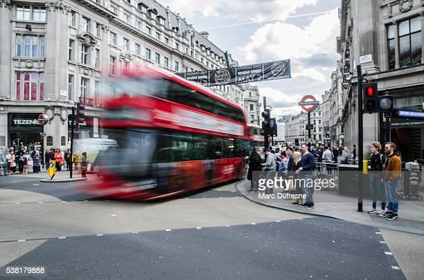 Long exposure of double decker bus with pedestrians