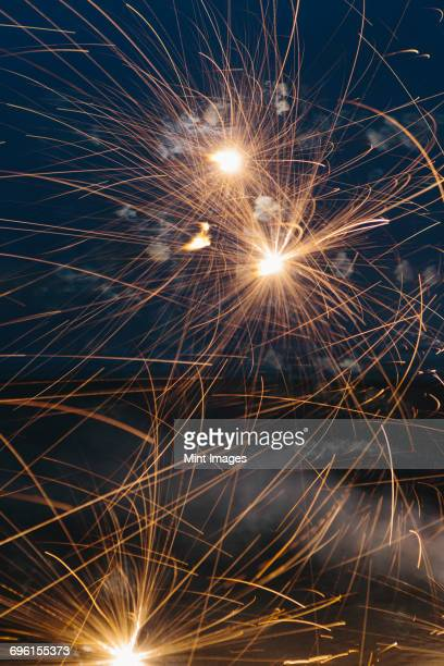 Long exposure of fireworks bursting into light over the beach at Long Beach Peninsula