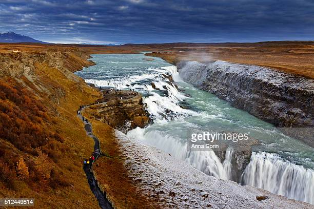 long exposure of gullfoss waterfall along golden circle route, iceland, in autumn with many tourists on scenic footpath - gullfoss falls stock photos and pictures