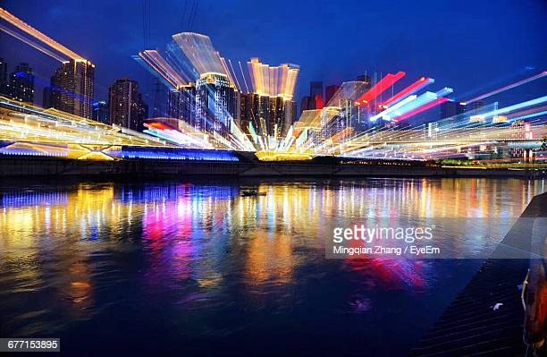 Long Exposure Of Illuminated Buildings By River At Night