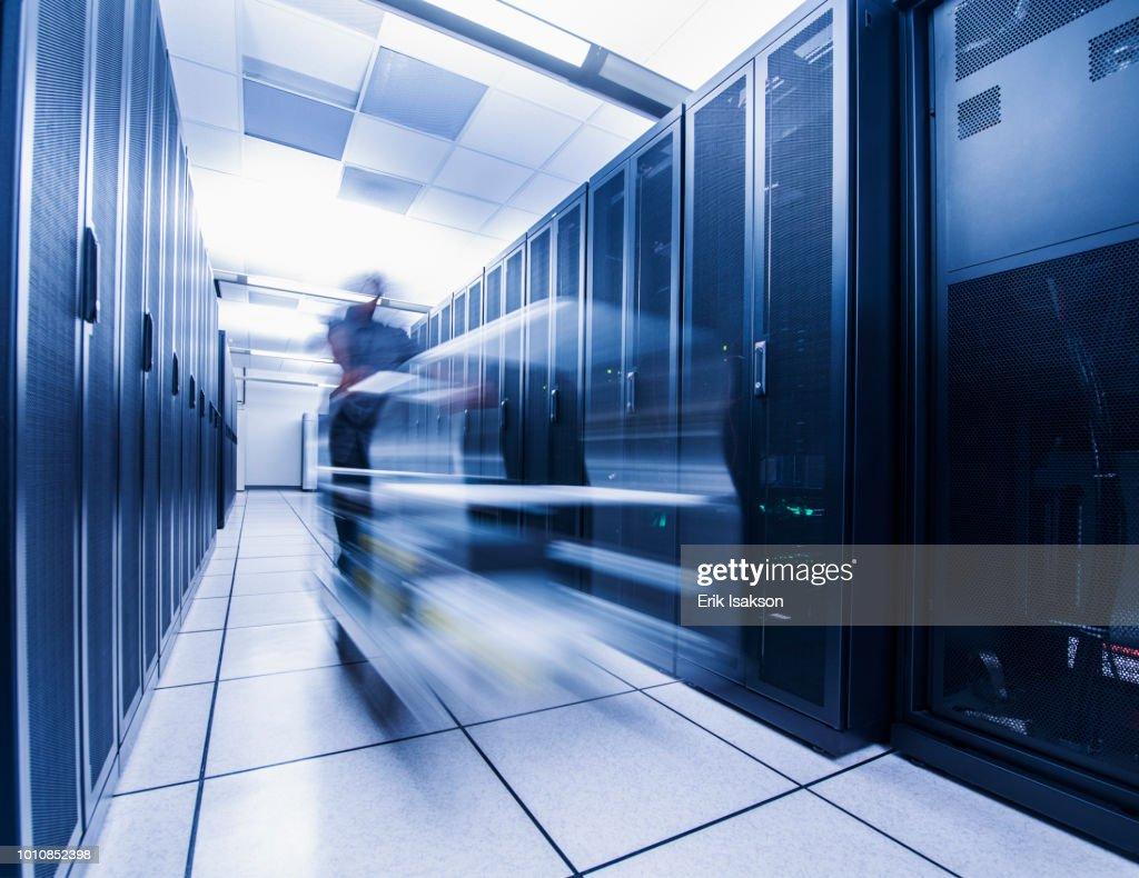 Long exposure of man pushing cart in server room : Stock Photo