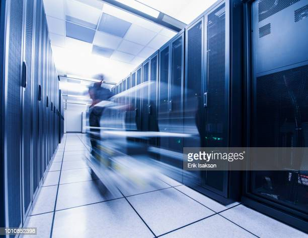Long exposure of man pushing cart in server room