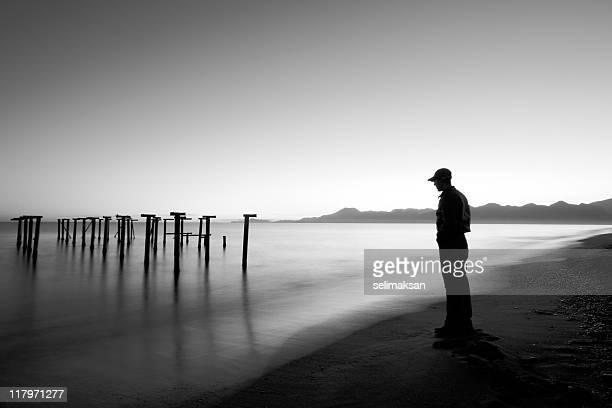 La exposición prolongada de hombre mirando olas en el puerto antiguo