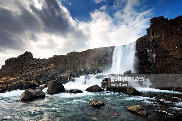 long exposure of oxarafoss waterfall in thingvellir national park, iceland, spring day - thingvellir stock photos and pictures