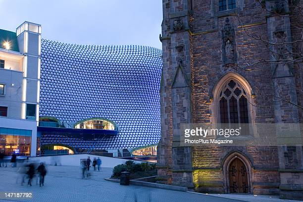 Long exposure of shoppers moving through the Bull Ring shopping district in Birmingham with St Martin's Church on the right and the iconic Selfridges...