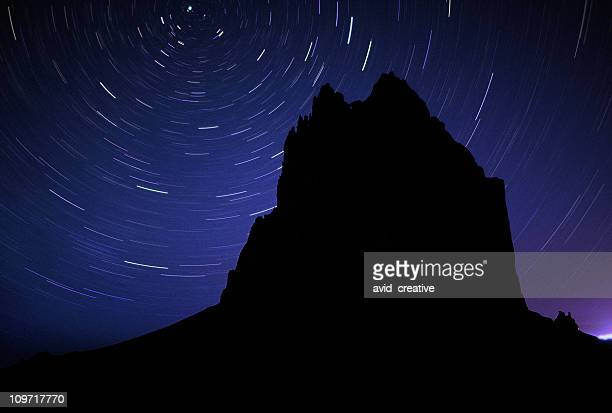 long exposure of stars and rock silhouette - shiprock stock photos and pictures