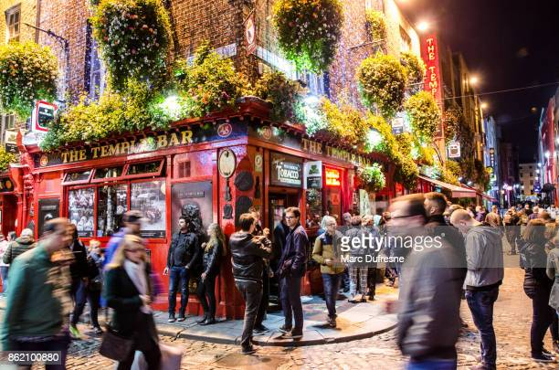 long exposure of temple bar in dublin with people drinking and walking by during night in autumn - republic of ireland stock pictures, royalty-free photos & images
