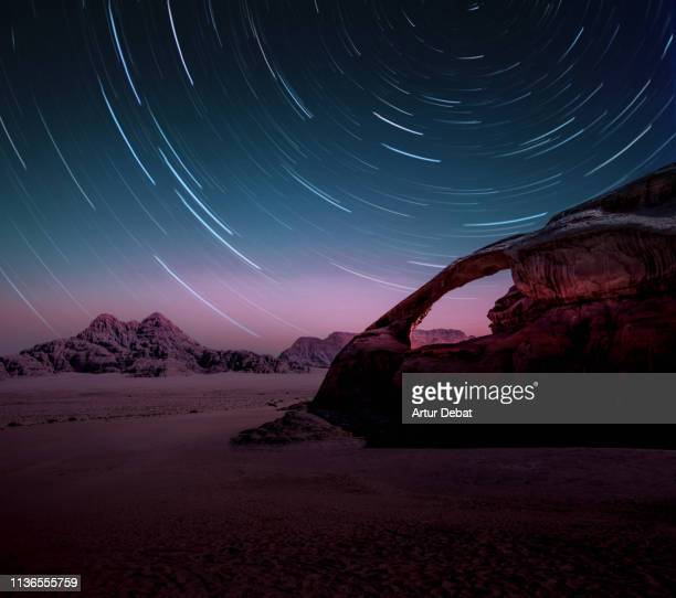 long exposure of the stars in the wadi rum desert of jordan with natural arch. - rock formation stock pictures, royalty-free photos & images