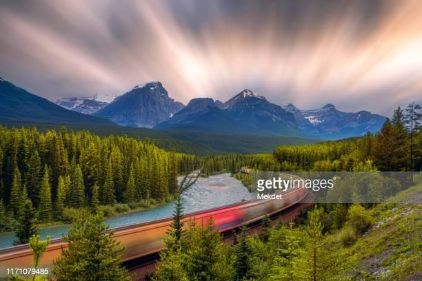 long exposure of the train at morant's curve, banff national park, canadian rockies, alberta state, canada - montañas rocosas canadienses fotografías e imágenes de stock