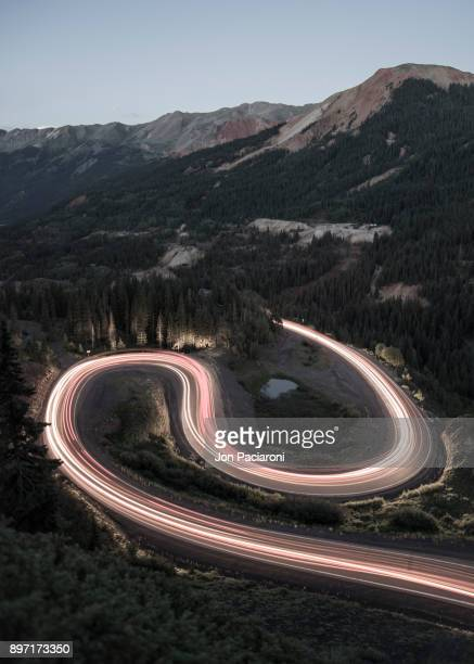 long exposure of traffic going up and over red mountain pass on the million dollar highway on a summer night - million dollar highway stock photos and pictures