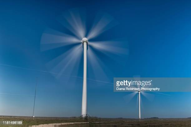 long exposure of two wind turbines along highway 20 in northern nebraska - turning stock pictures, royalty-free photos & images