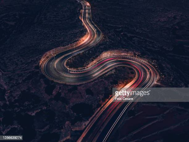 a long exposure of vehicles movement with blurring and light-trails on a winding road during the night. - industry stock pictures, royalty-free photos & images
