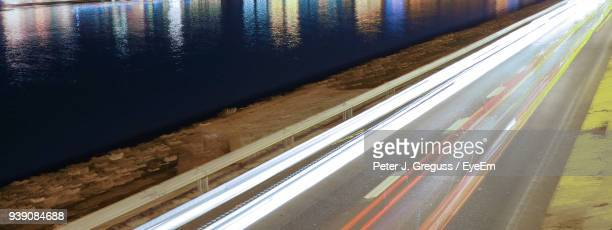 Long Exposure Of Vehicles On Road By River At Night