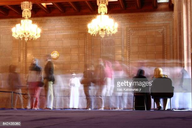 Long exposure of visitors moving in and out of the ladies prayer hall in the Sultan Qaboos Grand Mosque in Muscat, Oman